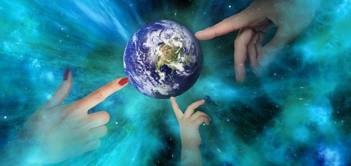 Modell der Welt - Weltkugel mit drei verschiedenen Händen, die darauf zeigen