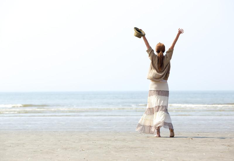 erfülltes Leben - Frau mit erhobenen Armen am Strand