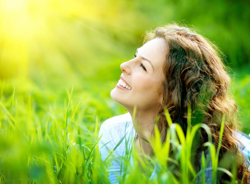 lächelnde Frau im Gras- sich selbst verzeihen