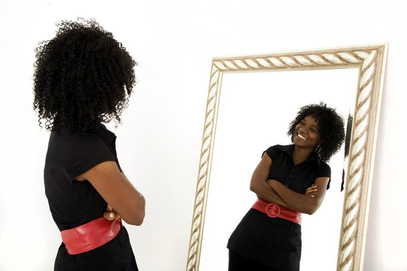 ein positives Selbstbild - Frau lächelnd vor dem Spiegel