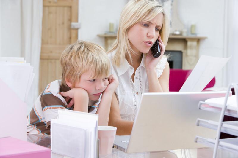 Abstand gewinnen - junge Frau die im Büro mit Laptop telefoniert, während der Junge sich langweilt