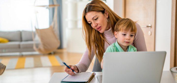 Erschöpfung - Mutter arbeitend mit Kind auf dem Schoß